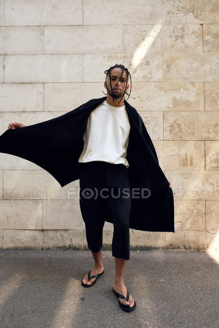 Fashionable young African American male in stylish outfit posing on street near grungy wall — Stock Photo