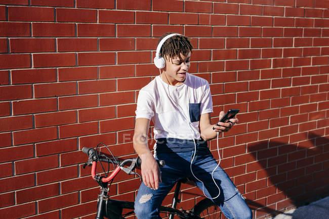 Giovane felice uomo nero ascoltare musica con smartphone in bicicletta — Foto stock