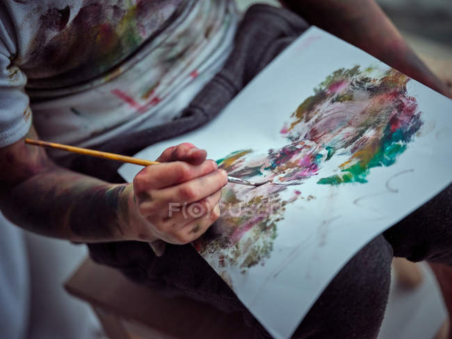 Cropped image of boy painting in smeared paper in workshop — Stock Photo