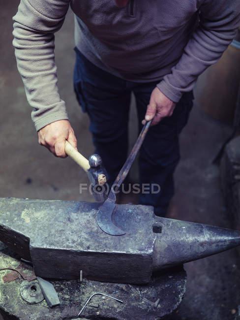 Ковальська ковка металу з молотком по старій ковадлі в традиційному семінарі — стокове фото