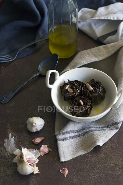 De délicieux artichauts frits avec de l'ail aromatique et de l'huile placés dans un bol en céramique près de la serviette et des ustensiles — Photo de stock