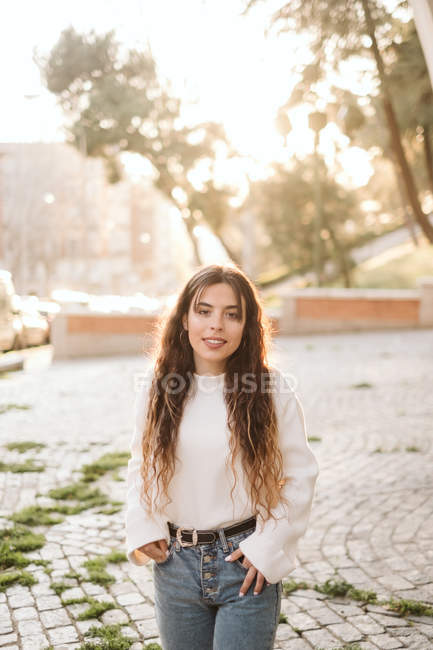 Pretty young woman in casual outfit smiling and looking at camera on sunny day on city street — Stock Photo