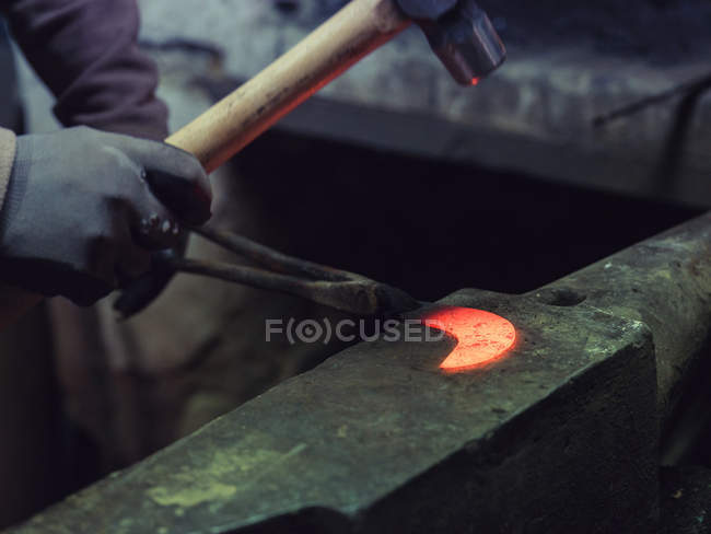 Blacksmith hands in gloves forging molten metal with hammer on ancient anvil in traditional workshop — Stock Photo