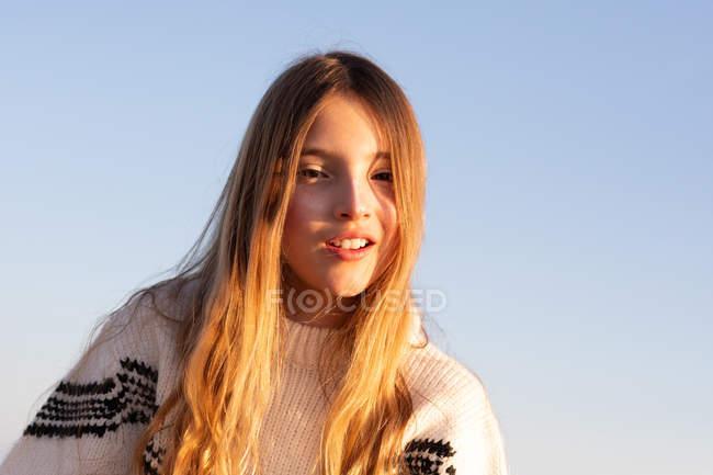 Adolescente femminile in maglione a maglia sorridente e guardando la fotocamera contro il cielo senza nuvole — Foto stock