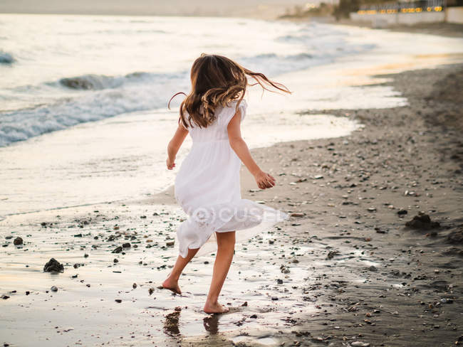 Little girl in white dress playing on seashore at sunset — Stock Photo