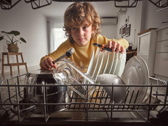 Хлопець з інструментами, ремонтуючи посудомийну машину на кухні. — стокове фото