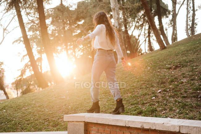 Молодая женщина в повседневной одежде растягивает руки, балансируя на заборе в солнечный день в парке — стоковое фото