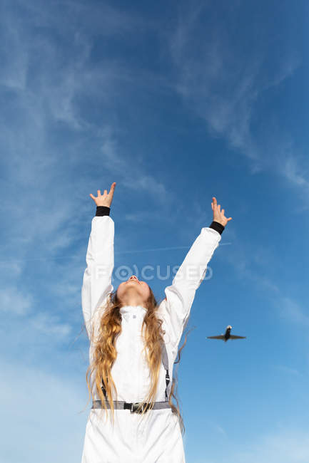 Teen girl with long hair raising hands while trying to reach flying aircraft against cloudy sky on sunny day — Stock Photo