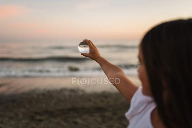Маленька жінка-дитина з каштанове волосся тримає скляну кулю на фоні хвиль — стокове фото