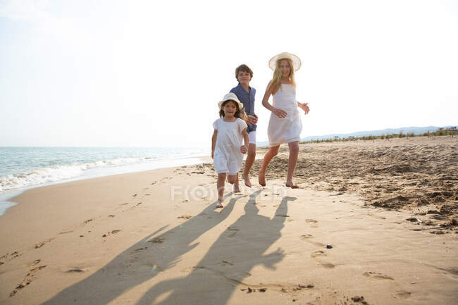Happy and smiling children in casual wear running barefoot along seashore on sandy beach in summer sunny day — Stock Photo