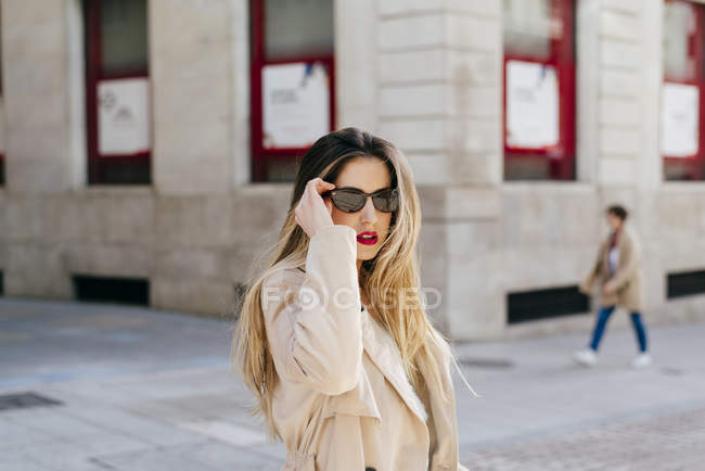 Young pretty female in stylish coat and sunglasses posing on street against marble building with bright red windows — Stock Photo