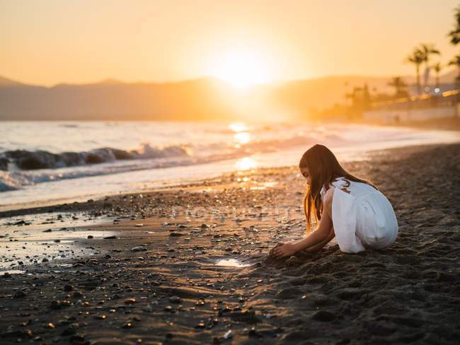 Cute pensive female kid in white dress playing with sand on seaside at sunset — стоковое фото