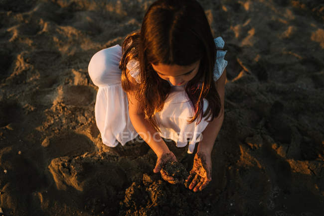 Cute pensive female kid in white dress playing with sand on beach in sunlight — Stock Photo
