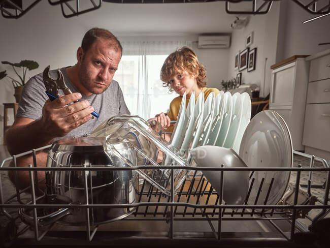 Розгніваний дорослий чоловік і хлопчик з інструментами ремонтуючи посудомийну машину на кухні. — стокове фото