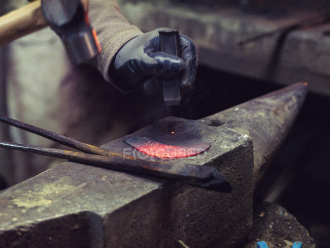 Blacksmith hand in gloves forging molten metal with hammer on ancient anvil in traditional workshop — Stock Photo