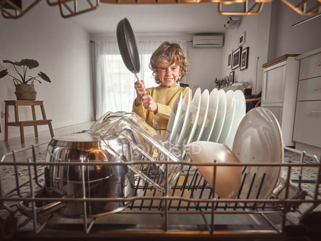 Annoyed menino gritando ao colocar frigideira em máquina de lavar louça aberta na cozinha — Fotografia de Stock