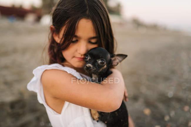 Портрет очаровательной девочки в белом платье, держащей маленькую собаку, сидя на песке — стоковое фото