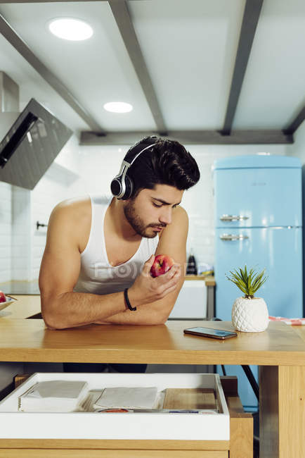 Young handsome male with stylish hairstyle in headset leaning on table in kitchen and holding ripe apple while looking at phone — Stock Photo