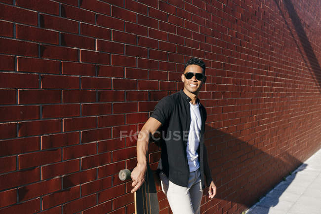 Young black man with long board leaning on wall — Stock Photo