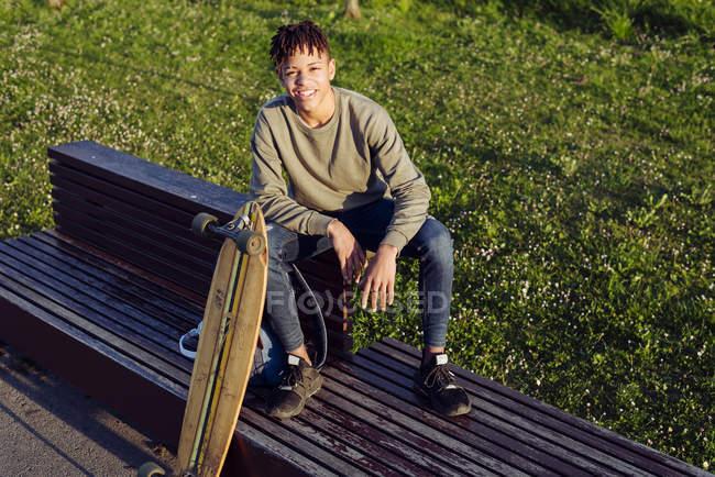Joven hombre negro sentado en el banco con monopatín - foto de stock