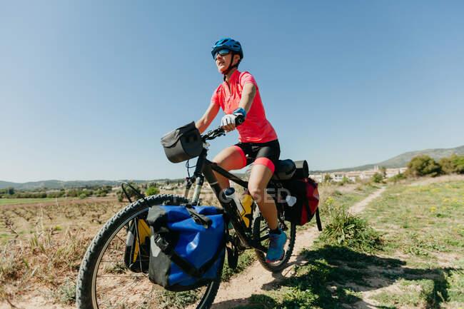 Леди в спортивной одежде и шлеме катается на велосипеде по каменистой дорожке, путешествуя по лесу в солнечный день в сельской местности — стоковое фото