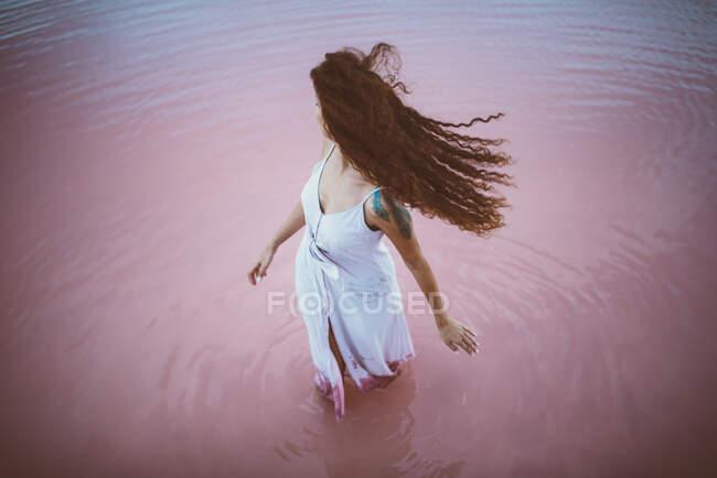 Молода красива жінка з довгим кучерявим волоссям у літньому вбранні, що насолоджується морським вітерцем. — стокове фото