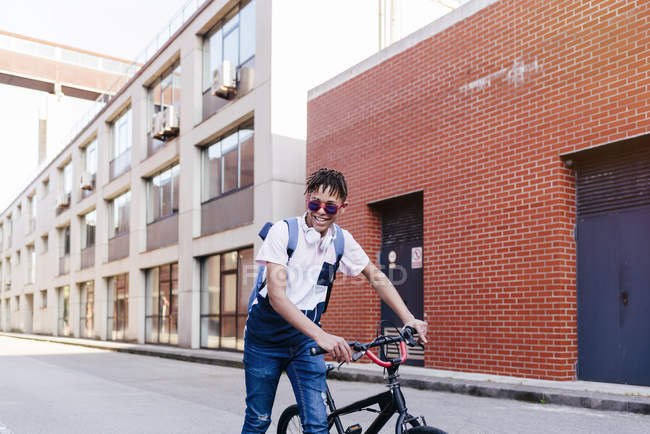 Young smiling black successful man with Afro hair in casual outfit and stylish sunglasses standing with bicycle on street — Stock Photo
