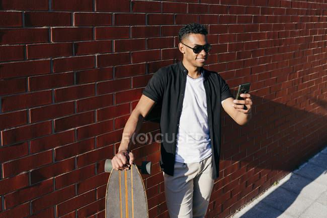 Jovem preto homem com longo bordo falando no telefone — Fotografia de Stock