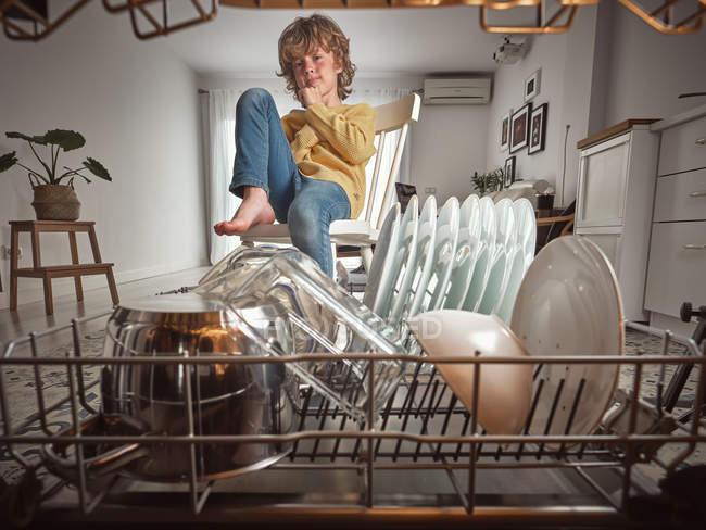 Garçon souriant regarder à l'intérieur lave-vaisselle ouvert dans la cuisine — Photo de stock