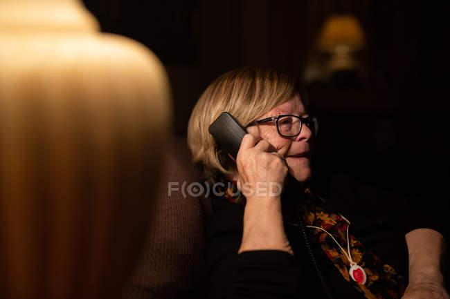 Mulher idosa feliz sorrindo e respondendo telefonema enquanto sentado no quarto escuro à noite em casa — Fotografia de Stock
