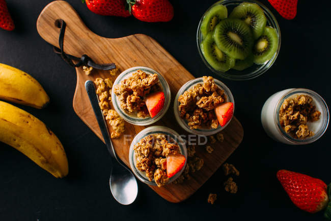 Glasses of cold tasty milk and delicious granola with fruits on wooden board — Stock Photo