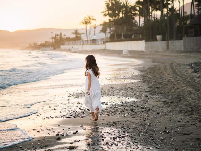 Side view of little girl in white dress walking on seashore on background of sunshine — Stock Photo