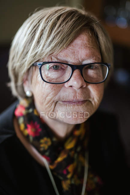 Senior woman with kind wrinkled face wearing spectacles and looking at camera while spending time at home — Stock Photo