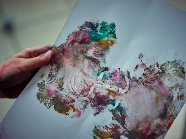 Cropped image of painted in bright colorful paints holding smeared paper in workshop — Stock Photo