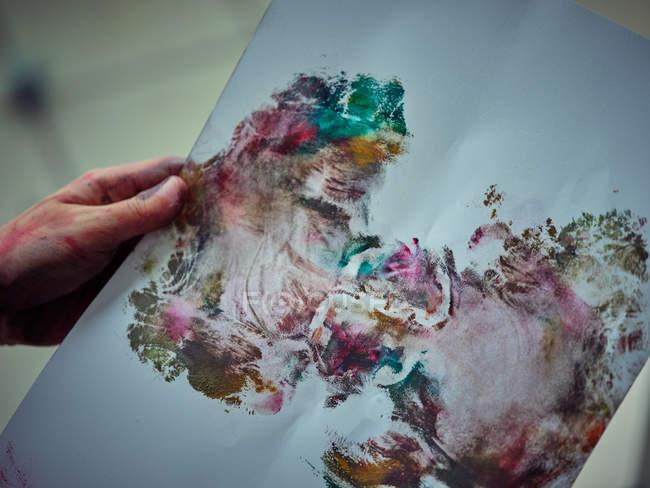 Zugeschnittenes Bild gemalt in hellen bunten Farben mit beschmiertem Papier in der Werkstatt — Stockfoto