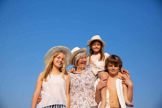 Sorridente nonna e nipoti in cappelli e abbigliamento estivo in piedi insieme nella giornata di sole — Foto stock