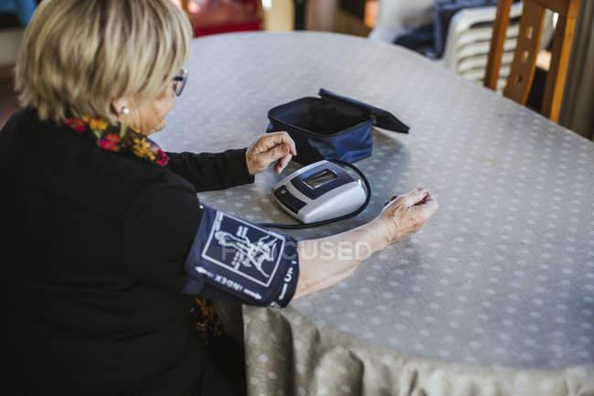 Старша жінка за допомогою тензіометра вимірює кров