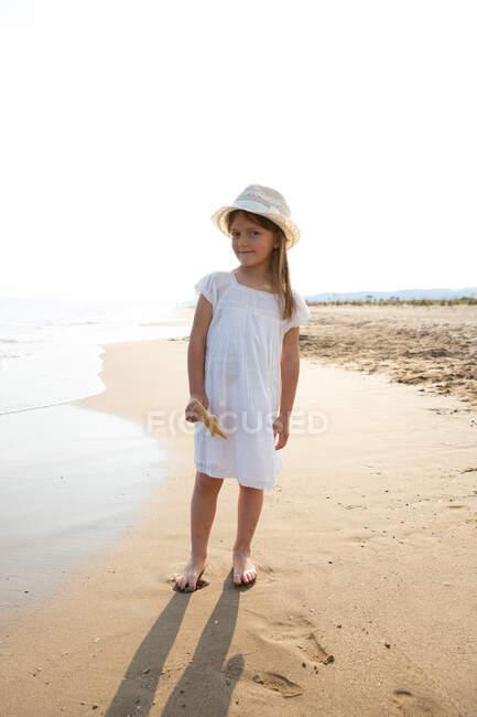 Menina muito séria com cabelos longos no chapéu segurando estrela do mar na praia no dia de verão — Fotografia de Stock