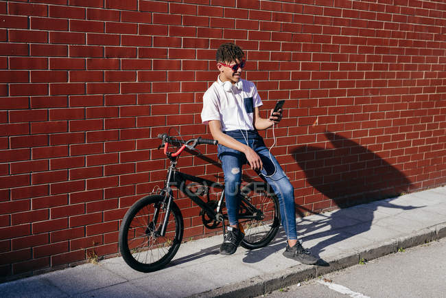 Young happy black man browsing smartphone on bike — Stock Photo
