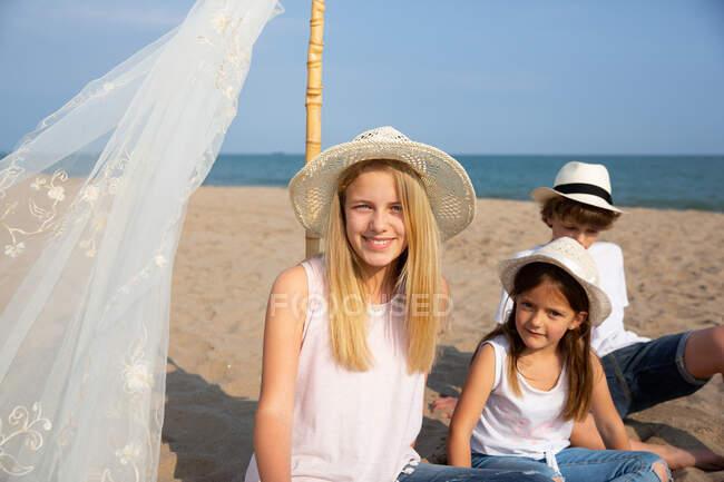 Bambini in cappelli seduti vicino alla tenda da sole sul palo sulla sabbia sulla spiaggia — Foto stock