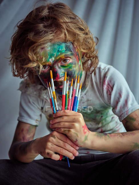 Красивий креативний хлопчик у повсякденному одязі, намазаний барвистими фарбами з пензлями. — стокове фото