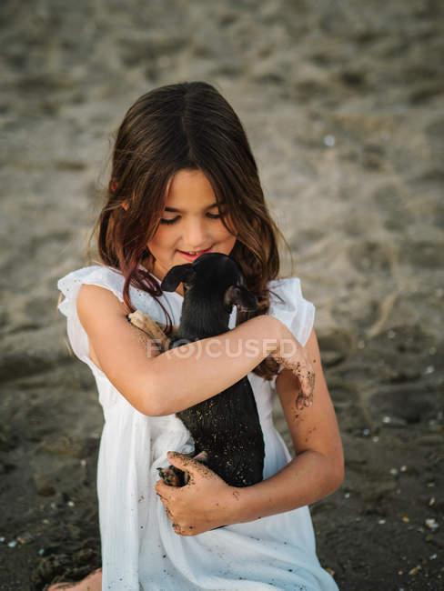 Ritratto di affascinante bambina in abito bianco che tiene il cagnolino seduto sulla sabbia — Foto stock