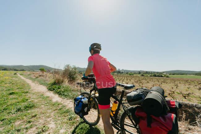 Dame in Sportbekleidung und Helm radelt auf steinigem Pfad durch den Wald an sonnigen Tagen in der Natur — Stockfoto