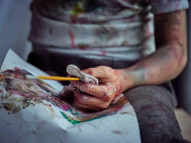 Закручений образ хлопчика в повсякденному одязі, намазаний барвистими фарбами сидячи на стільці і тримаючи щітку і серветку — стокове фото