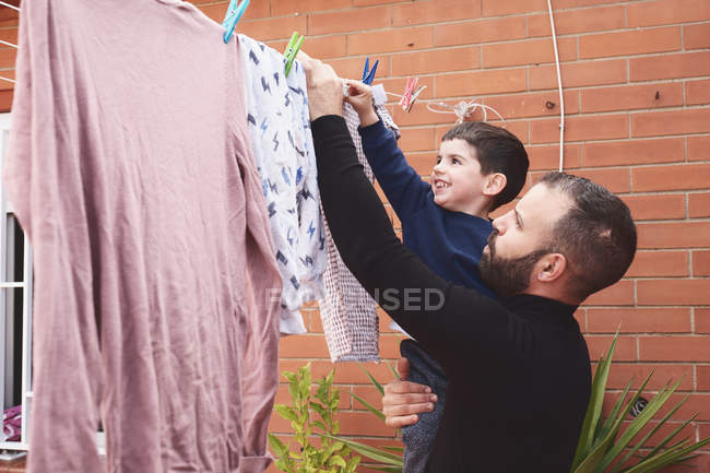 Bearded adult man holding smiling little boy while hanging wet clothes on rope on backyard together — Stock Photo