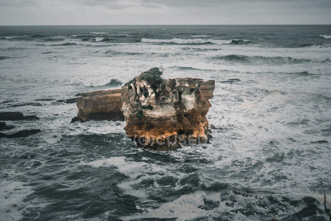 Landscape of lonely old rock among sea waves on cloudy day — Stock Photo