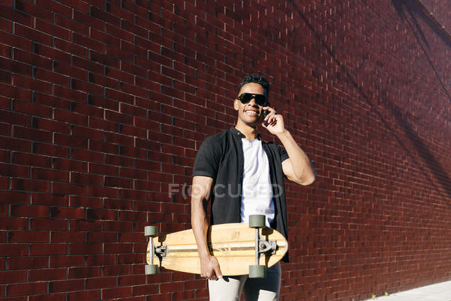 From below young African American cheerful handsome man in casual clothes and stylish sunglasses with long board speaking on phone — Stock Photo