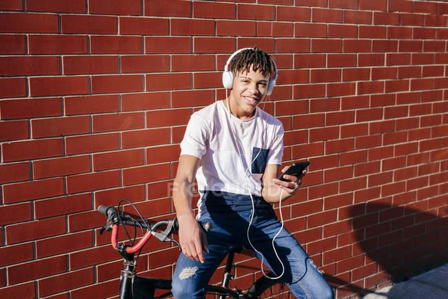 Jeune homme noir heureux écoutant de la musique avec smartphone à vélo — Photo de stock