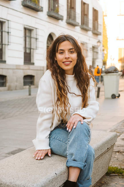 Pretty young female in casual outfit smiling and looking at camera on city street — Stock Photo