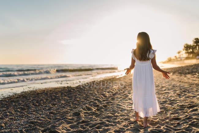 Little girl in white dress walking on seashore on background of sunset — Stock Photo